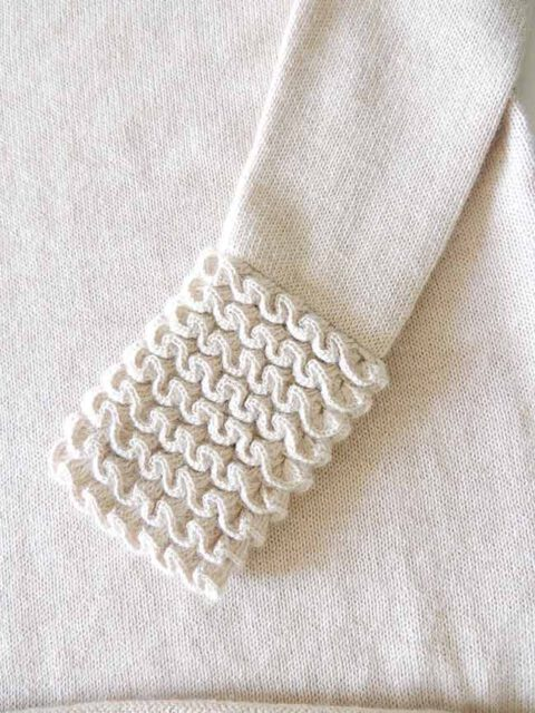 Knitted sweater light beige in soft baby alpaca with a round neckline, cuffs and neck rushes pattern.